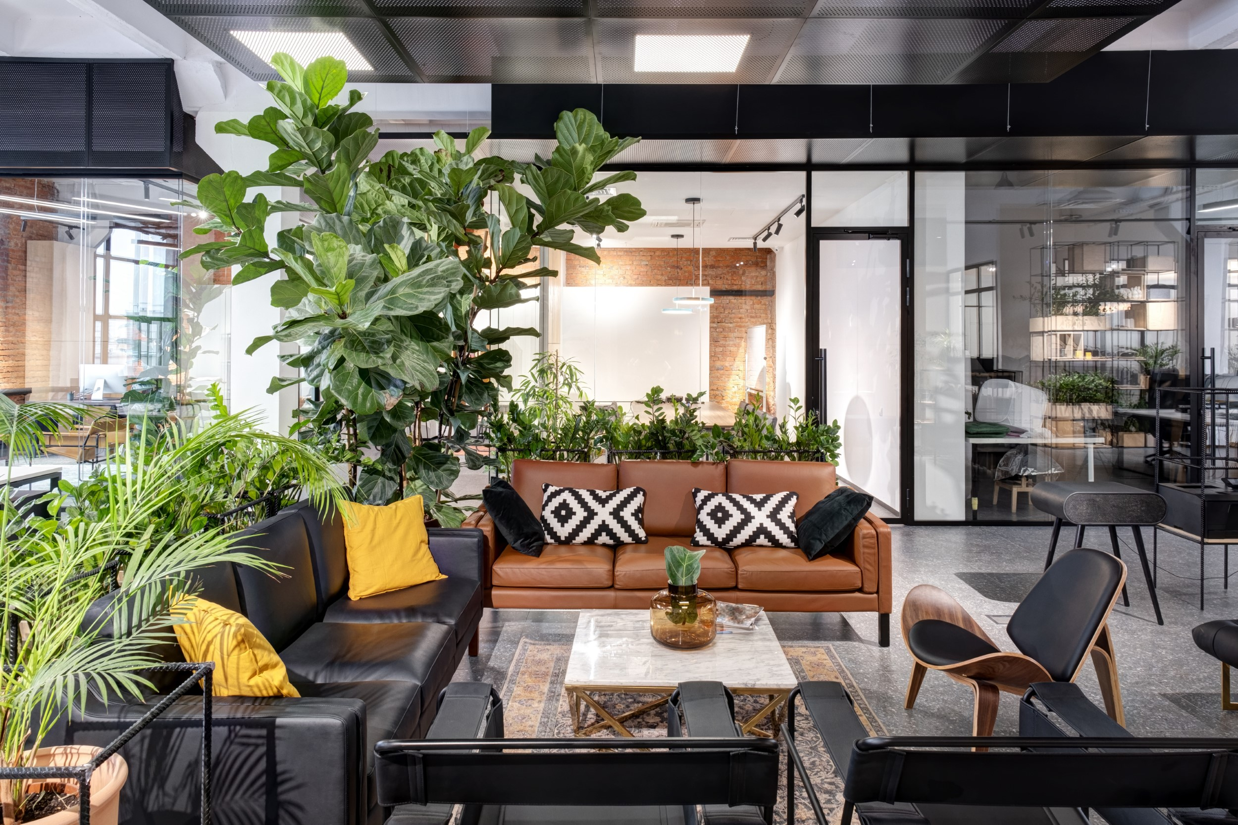 modern open space office interior with asitting area in the center among green spaces
